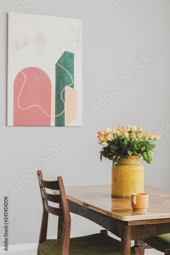roses in yellow glass vase on elegant wooden table in vintage dining room