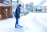 Man with snow shovel cleans sidewalks in winter during snowfall. Winter time in Europe. Young man in warm winter clothes. Snow and weather chaos in Germany. Snowstorm and heavy snowing. Schneechaos - 243458440