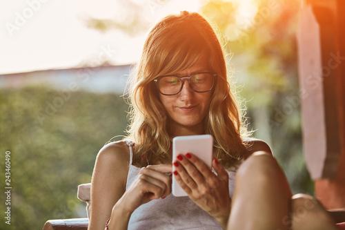 Leinwandbild Motiv Cute woman using smartphone on a porch sofa.