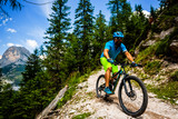 View of cyclist riding mountain bike on single trail in Dolomites, Cinque Torri, South Tirol, Italy - 243467244