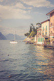 Idyllic italian lake landscape: Colorful houses, mountains and skye with clouds - 243473012