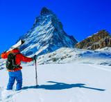 Man skiing on fresh powder snow with Matterhorn in background, Zermatt in Swiss Alps. - 243473054