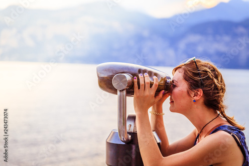 Sticker Young girl is curiously looking through binoculars, holiday