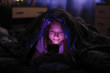 Leinwanddruck Bild Little girl at night looks at smartphone under a blanket in bed.