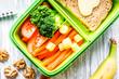 Leinwandbild Motiv green lunch box for kid on wooden background top view