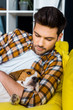handsome man in checkered shirt resting on sofa with dog