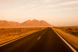 long straight road in the desert and a mountain at the end - 243492093