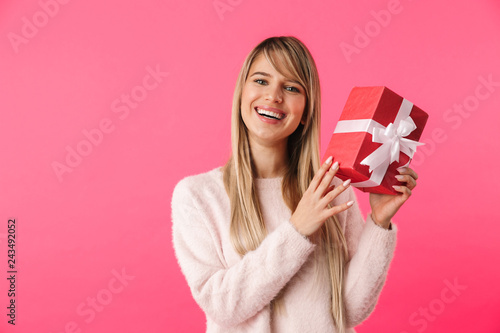 Cheerful young blonde girl standing isolated