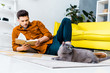 handsome man reading book and lying on floor with british shorthair cat in living room