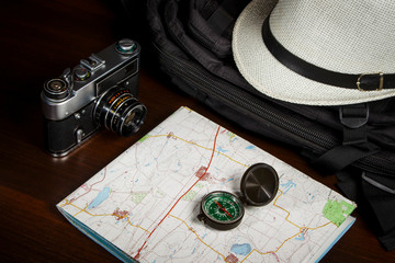 Compass on the map near the backpack with a hat
