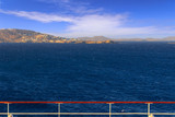 Panoramic view of Mykonos from cruise ship deck. Sea horizon in the wind: coast of Greece in the Aegean islands. Scenery of rocky coastline: azure waters of the Aegean Sea, cliff, rocks and stones.  - 243498669