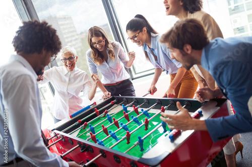 Leinwandbild Motiv Employees playing table soccer indoor game in the office during break time