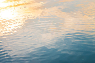 Golden light reflected on the surface of the evening water. © adisorn123