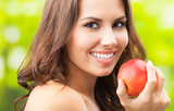 Young happy smiling woman with apple, outdoors - 243515220