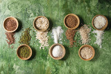 Variety of raw uncooked grains superfood cereal linen seeds, sesame, mung bean, wheat, buckwheat, oatmeal, coconut, rice in wooden bowls over green texture background. Flat lay, space - 243515499