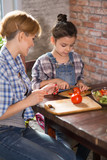 Mom and daughter cook together at home - 243517821
