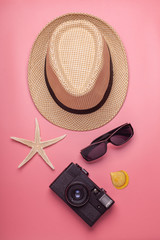 hat, starfish, shell, camera, sunglasses on pink background, travel concept, vertical photo © Schum
