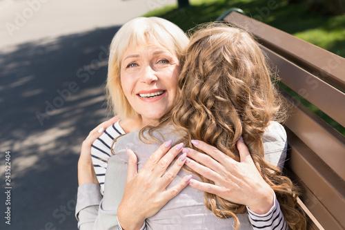 Foto Murales Elderly mother embracing with daughter in park