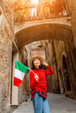 Traveler woman with flag in narrow street in Italy