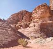 Woman climbing on rocks in Wadi Rum , Jordan