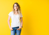 Beautiful young blonde woman smiling standing over isolated yellow background - 243529238