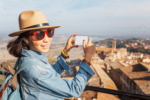 Sticker Happy asian tourist woman with smartphone in old town of Montepulciano, Tuscany. Vacation and travel in Italy concept