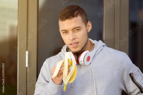Banane Frucht essen junger Mann isst Sport Training Jogger Fitness