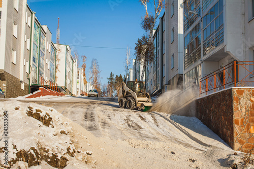snow removal machine at work at an apartment house - 243533664