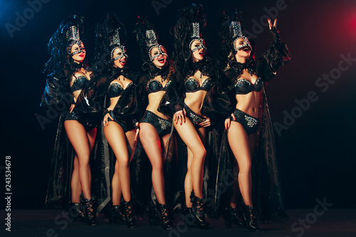 fototapeta na ścianę The group of young happy smiling beautiful female dancers with carnival dresses posing on black studio background
