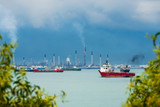 View of the Singapore Strait from Sentosa Island. Ships, industrial landscape and stormy weather. - 243561664