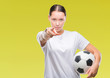 Leinwandbild Motiv Young beautiful caucasian woman holding soccer football ball over isolated background pointing with finger to the camera and to you, hand sign, positive and confident gesture from the front