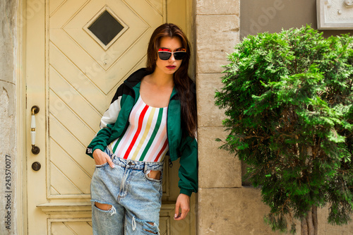 Portrait of a girl in clothes in the style of the 90s, sporty style, jacket, jeans, bananas, sunglasses. Old city, on the background of a vintage door