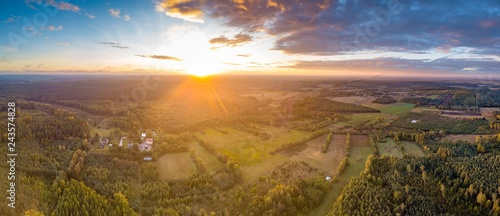 Beautiful sunrise with colorful sky over forest and meadows - 243574828