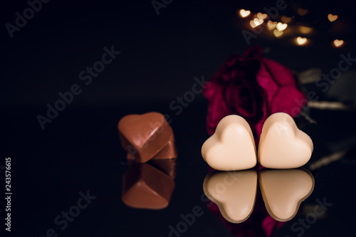 Heart shaped chocolates and red rose on black background