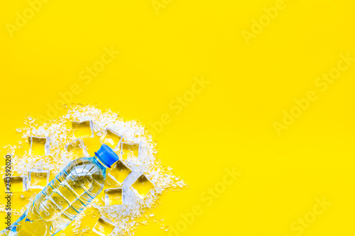 Leinwandbild Motiv Bar desk with ice cubes and plastic bottle on yellow background top view space for text