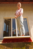 Woman cleaning patio using brush broom - 243625039