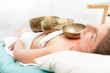 Quadro Young woman lying on bed in spa receiving sound therapy with singing bowl on her body