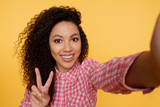 Excited black girl in pink attire laughing while making selfie. Indoor portrait of gorgeous african female model taking picture of herself showing peace sign with fingers - 243627663