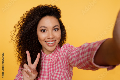 Excited black girl in pink attire laughing while making selfie. Indoor portrait of gorgeous african female model taking picture of herself showing peace sign with fingers