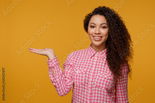 Portrait of a happy smiling young girl standing isolated over blue background. Looking camera pointing