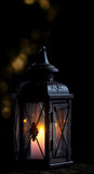 Lantern with candle in front of dark background - 243641440