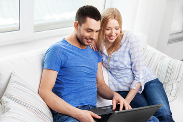 technology, internet and people concept - happy couple with laptop computer at home