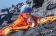 Leinwandbild Motiv cute young baby enjoys exploring the black sand at the beach