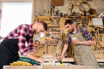 profession, carpentry, woodwork and people concept - two carpenters working and drinking coffee at workshop