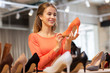 sale, shopping, fashion and people concept - happy young woman choosing shoes at store