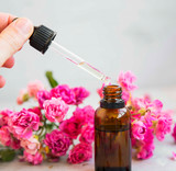 Rose oil bottle and dropper, aromatherapy and spa with roses flowers, spa setting - 243648850