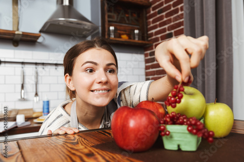 Leinwandbild Motiv Happy young woman standing at the kitchen at home