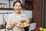 Happy young woman at the kitchen at home