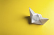 Leinwanddruck Bild - Paper boat on a yellow background with copyspace