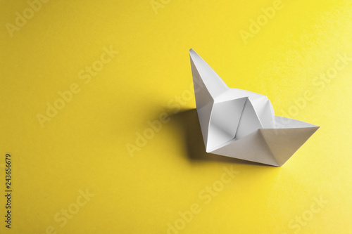 Leinwanddruck Bild Paper boat on a yellow background with copyspace